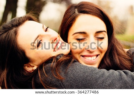 Girl hugging her best friend. In the park