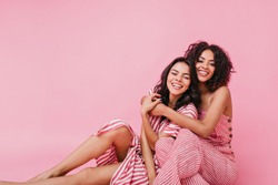 Girl hugs her cousin and gently looks into camera. Sisters in cute clothes pose with smile for summer photo shoot
