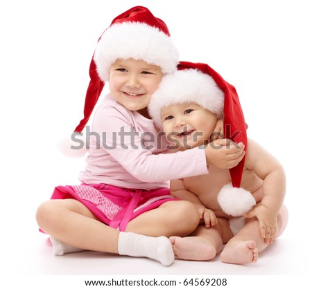 Girl hugs her little brother, both wearing red Christmas caps and smile, isolated over white