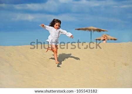 Girl hurries on sand - stock photo