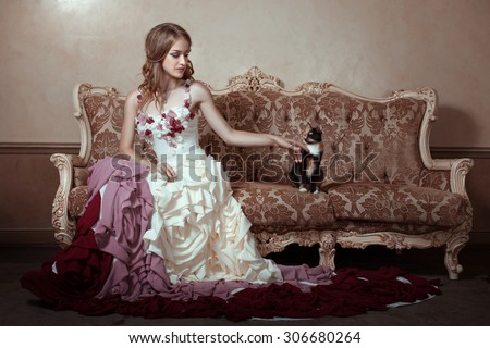 Girl in a beautiful dress with a train. She is sitting on an old couch.