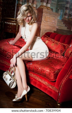 girl in a beige dress on the red couch