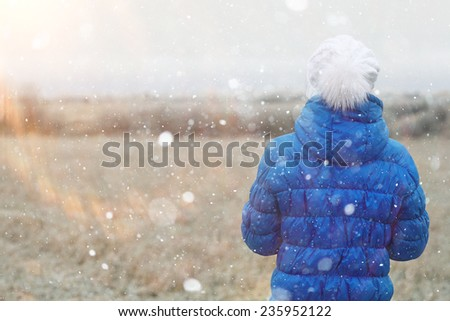 girl in a blue down jacket winter view from the back