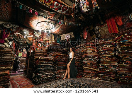 Girl in a carpet store. Happy woman customer choosing colored carpet in carpet store. Girl in Turkish market with amazing colorful carpets. Cheerful woman customer shopping carpet in interior store