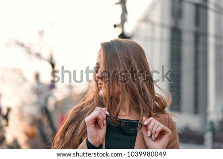 girl in a coat walking around the city #1039980049