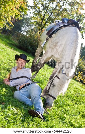 Girl in a cowboy hat lies on the grass near a white horse