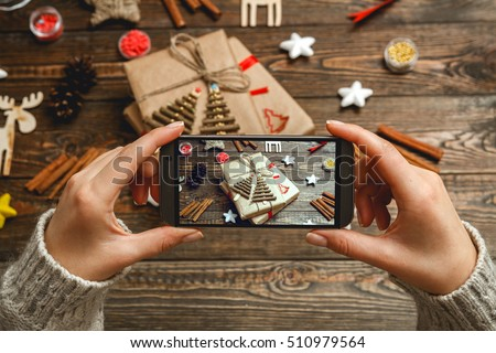 Girl in a cozy knitted sweater makes the photo on the phone Christmas accessories and handmade gifts on dark wooden desk