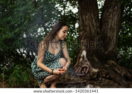 Girl in a dress is checking a barbecue sausage. Camping nature, rain.