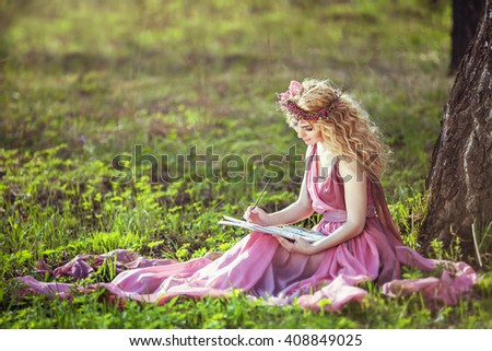 Stock Photo Girl in a fairy dress sitting under a tree in the woods and draws
