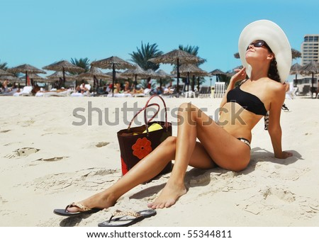 girl in a fashionable black bathing suit   and hat on the beach