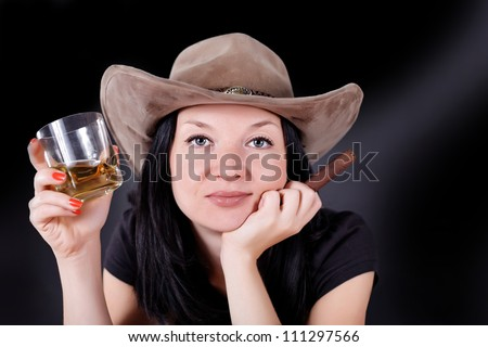 girl in a hat with a cigar and whiskey dark background