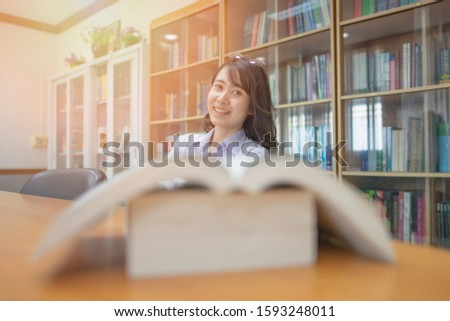 Girl in a library with big books in the foreground and bookshelves on the background, selective focused picture of beautiful female student smiling while sitting in a reading room, education concept