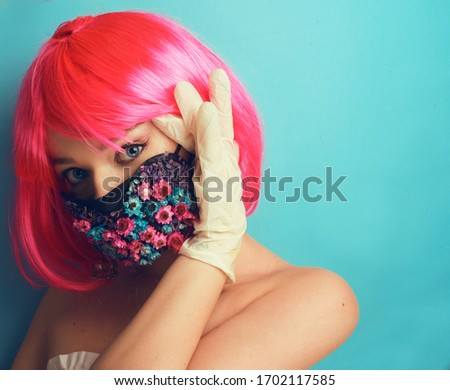 Girl in a mask and gloves, fashion photo. A model with pink hair posing in a studio in a mask of flowers and gloves, spring