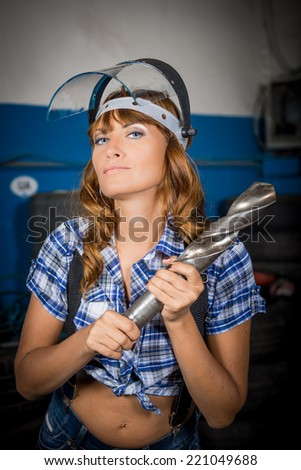 Girl in a mask of glass. Girl and drill. An employee in the garage. sexy worker