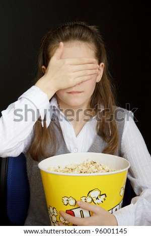 girl in a movie theater closes her eyes