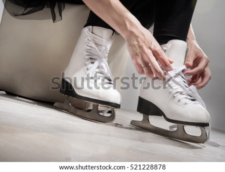 Girl in a new white skates for skating on ice sitting on the ice.