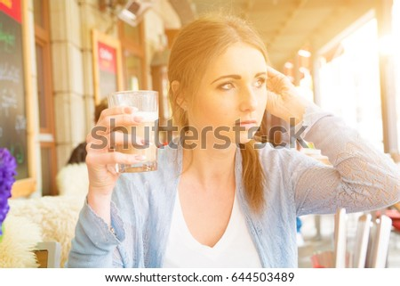 girl in a outdoor cafe with a glass of cappuccino in   hand