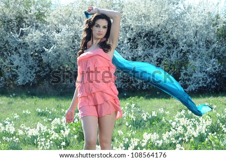 girl in a pink dress plays with a blue ribbon in a field of daisies