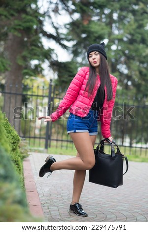 girl in a pink jacket standing on one leg