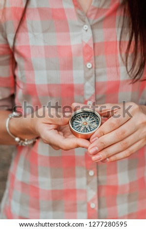 Girl in a plaid shirt holding a compass. Magnetic compass orientation