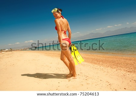 girl in a red bikini with a mask and flippers on beach