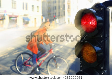Girl in a red coat on a bicycle at the intersection of the city for a red traffic light in spring day