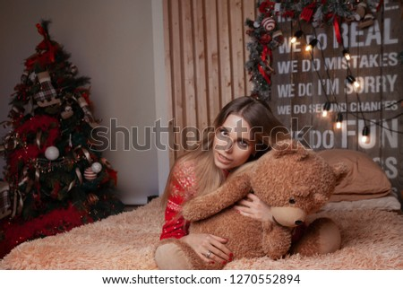 Stock Photo girl in a red sweater lying on the bed with a soft toy, soon the new year and Christmas