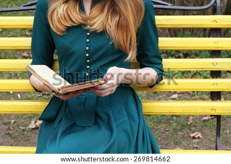 Girl in a romantic gown with a book in her hands. Pastime, recreation, relaxation, Hobbies, leisure. Reading books. Young woman on  the bench. Dreamer. The atmosphere of romance and tranquility.