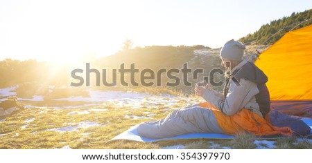 Girl in a sleeping bag sitting near the tent and was holding the Cup. #354397970