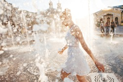 Girl in a spray of water in a fountain