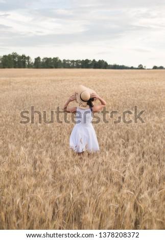 girl in a straw hat in a wheat field #1378208372