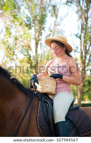 Girl in a straw hat riding a horse looking into a basket