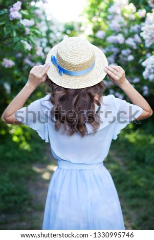 Girl in a straw hat with a blue ribbon on a spring afternoon. Back view. Trendy casual summer or spring outfit. Street fashion. Woman in a boatman's straw hat. The concept of female spring fashion