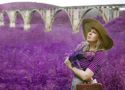 Girl in a summer hat on a background of a bridge on a sunny day. middle age Woman in wide brim hat by railroad bridge with violet  bouquet. purple wild flowers. summertime season.