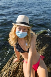 girl in a swimsuit, a hat and a medical mask sits on a stone on the sea coast. Rest during quarantine, pandemic  covid - 19. Summer recreation in the fresh air near the sea. Sunny day, summer mood