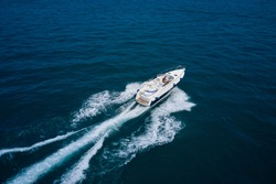 Girl in a swimsuit driving a large yacht in motion. White high-speed yacht in motion on blue water top view. High speed, Water splashing. Aerial view luxury motor boat. Back view