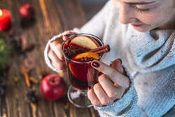 Girl in a warm sweater is holding a glass of mulled wine. Concept of a festive mood, a magical cozy atmosphere with a mug of traditional hot beverage.