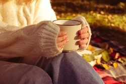 girl in a warm white sweater holds Cup of coffee. Autumn background, the concept of warmth and comfort