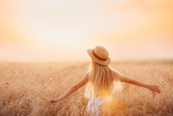 Girl in a wheat field looks at the sunset