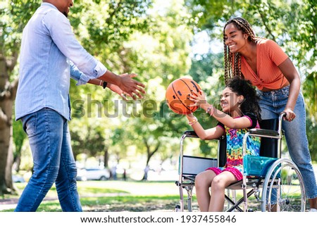 Girl in a wheelchair playing basketball with her family. Photo stock ©