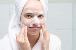 girl in a white bathrobe in the bathroom soaps her face with acne skin