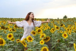 Girl in a white dress among blooming sunflowers