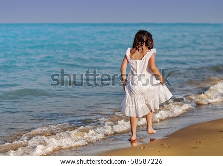 Girl in a white dress going along the sea bank