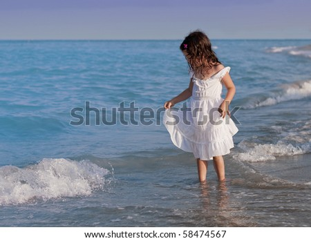 Girl in a white dress playing with water on a sea bank
