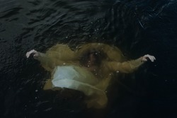 Girl in a white dress under water. A woman drowns in a lake. Folklore.