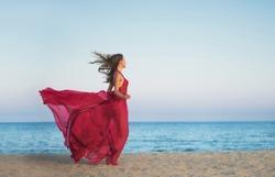 Girl in airy dress running along the beach