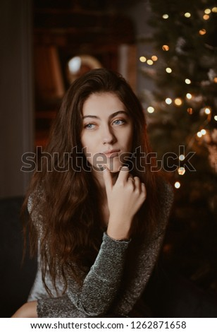 Girl in an elegant dress sitting on the sofa near the Christmas tree.  Girl with long hair, new year interior.  #1262871658