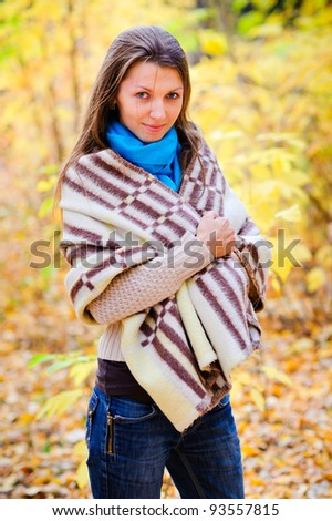 girl in autumn forest with a blanket