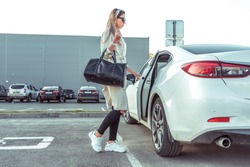 Girl in autumn in city parking lot, in summer car. He opens door takes out removes shopping bag. White business sedan. Parking mall. Woman in raincoat with black leather bag