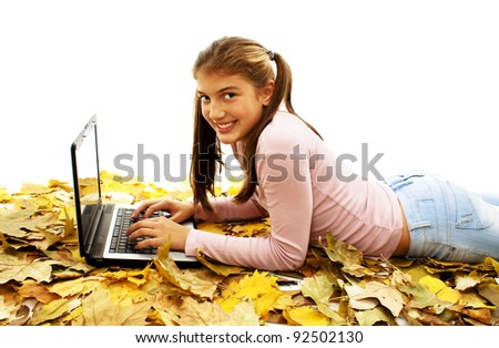 Girl in autumn leaves with laptop. Studio shoot